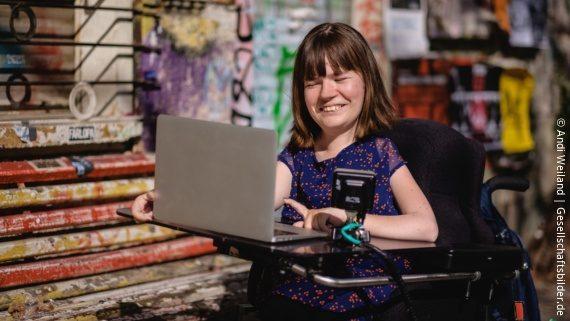 Foto: Eine junge Frau sitzt in ihrem Rollstuhl und lächelt zugewandt zum Bildschirm ihres Laptops, der vor ihr steht.; Copyright: Andi Weiland   Gesellschaftsbilder.de