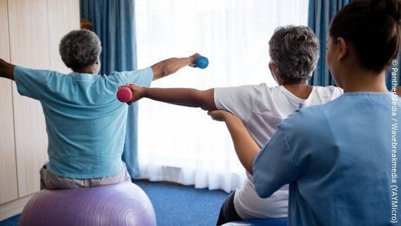 Foto: Senioren werden beim Training mit Hanteln von einer Pflegekraft unterstützt; Copyright: PantherMedia / Wavebreakmedia (YAYMicro)