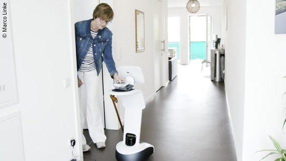 Foto: ein Roboter steht vor der Zimmertür einer Frau; Copyright: Marco Linke