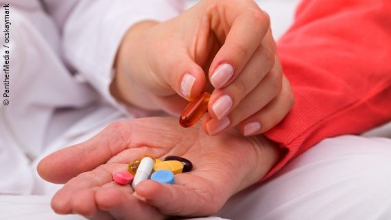 Photo: a person laying pills in another persons hand; Copyright: PantherMedia / ocskaymark