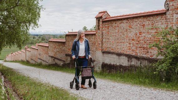 Foto: eine Frau, die mit ihrem Rollator auf einem Schotterweg unterwegs ist; Copyright: Saljol GmbH