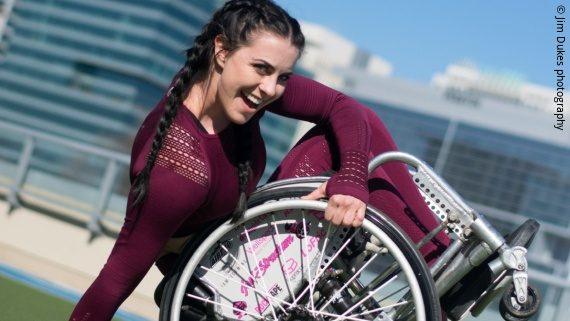 Foto: eine junge Frau in weinroten Trainingssachen sitzt in einem Rollstuhl und macht einen halben Backflip – Jesi Stracham; Copyright: Jim Dukes Photography