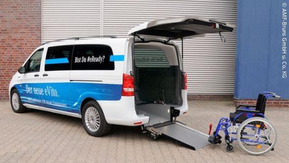 Foto: ein weißer Kastenwagen mit Rollstuhlrampe, dahinter steht ein blauer Rollstuhl; Copyright: AMF-Bruns GmbH & Co. KG